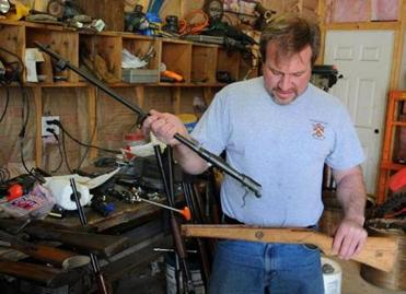Bill Bachant works on a Japanese rifle at his shop in Lakeville. Items beyond repair, he says, he sells for parts.